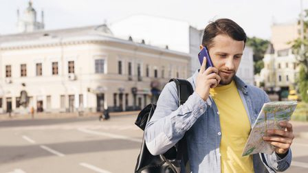 Charming-young-man-looking-map-while-talking-cell-phone-street_23-2148203047_thumb_main